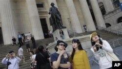 中国游客在纽约证交所大楼外拍照留念(资料图)
