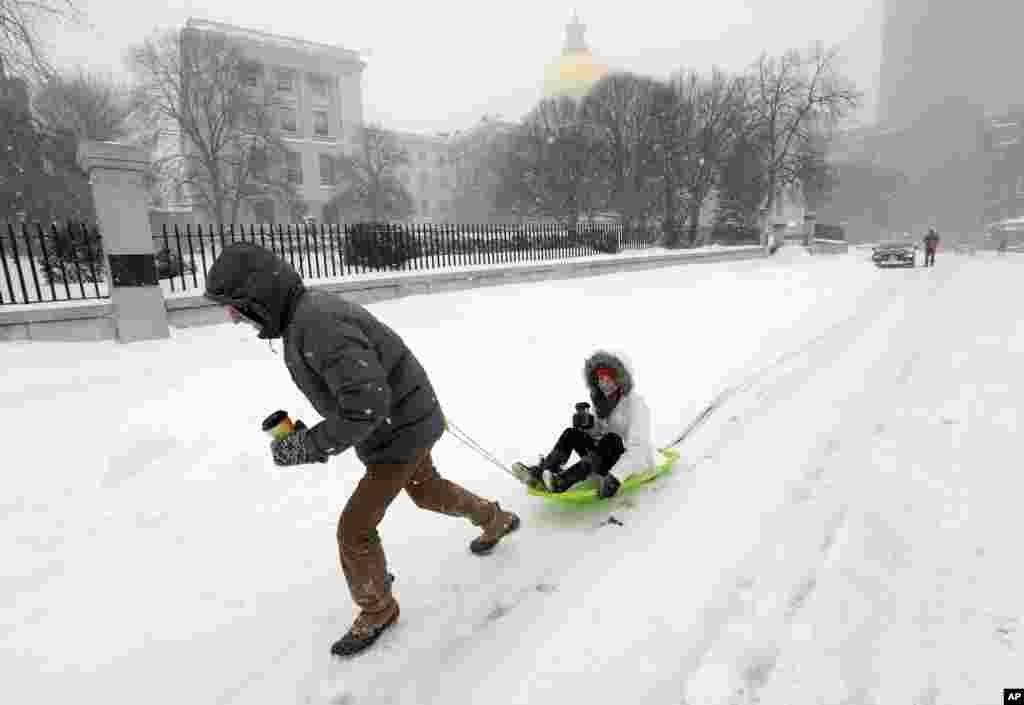 John Joy pulls his girlfriend Brooke Finan past the Statehouse after they made a search for coffee during a winter snowstorm in Boston, Massachusetts, Jan. 27, 2015.