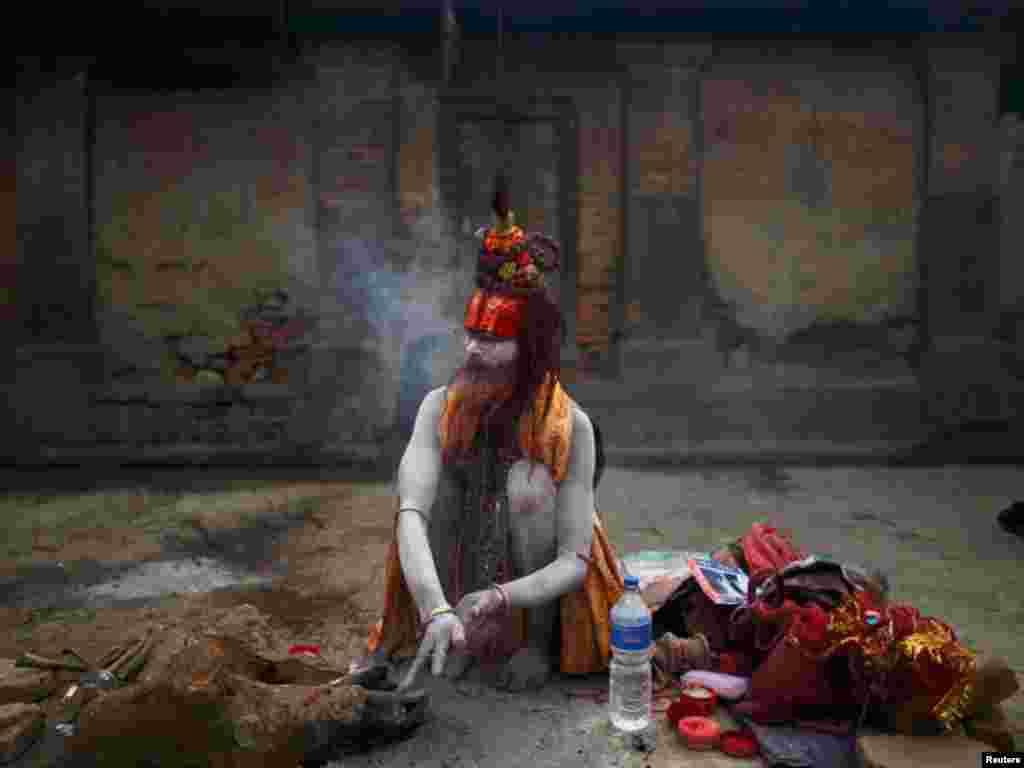 نیپال میں ہندووں کے مذہبی تہوار میں اپنے خدا شیوا کی ہندو یاتری پوجا کرتے ہیں اور آگ جلاکر کوئلے کی راکھ جسم پر ملتے ہیں