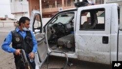 Polisi Irak memeriksa mobil yang hancur akibat ledakan bom bunuh diri dekat sebuah TPS di Kirkuk, Irak, Senin (28/4). Serangan hari Rabu (30/4) di Kirkuk saat pelaksanaan pemilu parlemen menewaskan 2 orang perempuan.