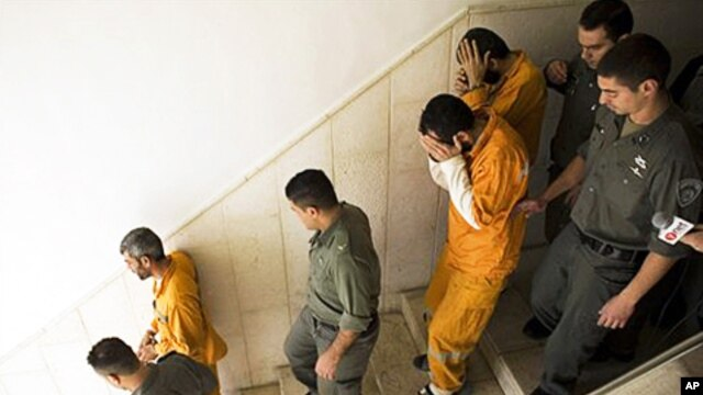 Palestinians suspected of killing Kristine Luken, an American tourist in December 2010, are escorted by Israeli security officers at the district court in Jerusalem, 26 Jan 2011