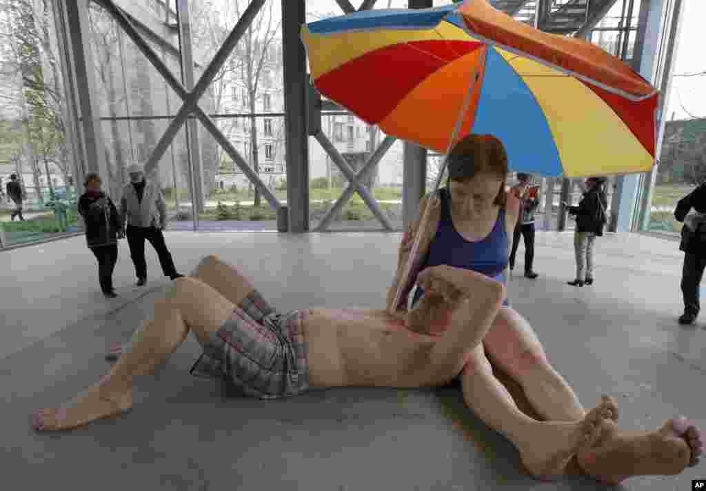 Khách xem tác phẩm cặp vợ chồng dưới ô dù của nhà điêu khắc Ron Mueck người Australia đang triển lãm ở Paris, Pháp.