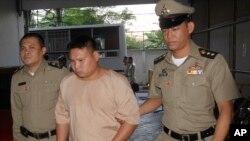 """Les agents de l'ordre escortent Vivat Yodprasit, le """"tireur au popcorn"""", au centre, à l'arrivée à la cour pénale à Bangkok, en Thaïlande, 3 mars 2016."""