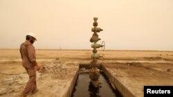 Seorang pekerja berjalan melewati sumur minyak di lapangan minyak Sindbad dekat perbatasan Irak-Iran di Basra, Irak, 23 April 2018.