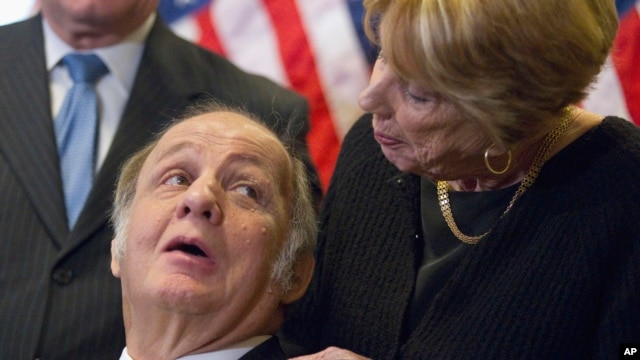 FILE - This March 30, 2011 file photo shows former White House press secretary James Brady, left, who was left paralyzed in the Reagan assassination attempt, looking at his wife Sarah Brady, during a news conference on Capitol Hill.