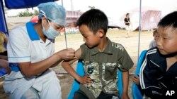 2008年6月1日,中國軍醫在四川省桃花山一處災民棲身營地為兒童注射甲肝疫苗。(資料照)