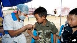2008年6月1日,中国军医在四川省桃花山一处灾民栖身营地为儿童注射甲肝疫苗。