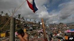 """菲律宾中部塔克洛班市(又译""""独鲁万""""):菲律宾国旗和擦泪的幸存者"""