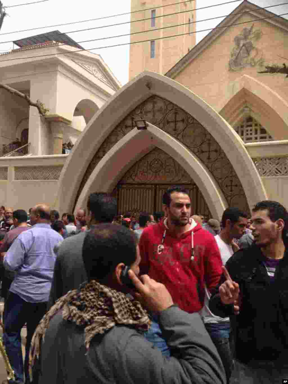 Familiares e transeuntes reúnem-se à porta da igreja depois do ataque suicida à bomba na cidade de Tanta no Delta do Nilo. O ataque aconteceu no Domingo de Ramos, que dá início à semana santa e culmina com a Páscoa. Abril 9, 2017.