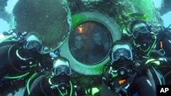 Des astronautes devant Aquarius, module sous-marin installé par la NASA au large de la Floride