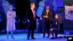 In this photo provided by The Public Theater, Tina Benko, left, portrays Melania Trump in the role of Caesar's wife, Calpurnia, and Gregg Henry, center left, portrays President Donald Trump in the role of Julius Caesar during a dress rehearsal of The Public Theater's Free Shakespeare in the Park production of Julius Caesar, in New York. Rounding out the cast on stage is Teagle F. Bougere as Casca, and Elizabeth Marvel, right, as Marc Anthony. (Joan Marcus/The Public Theater via AP)