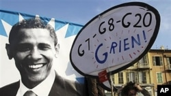 Demonstrators walk past of poster of U.S. President Barack Obama with a placard reading 'G7-G8-G20-I have nothing' during a protest in Nice, southern France, Nov. 1, 2011.