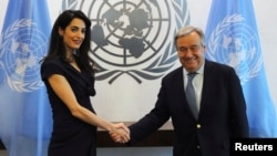 International human rights lawyer Amal Clooney shakes hands with United Nations Secretary General, Antonio Guterres, at U.N. headquarters in New York, March 10, 2017.