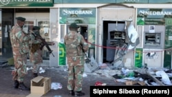Members of the military look at damaged ATM machines outside a bank as the country deploys army to quell unrest linked to jailing of former President Jacob Zuma, in Soweto, South Africa, July 13, 2021. REUTERS/Siphiwe Sibeko