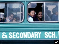 FILE - Kenyan students ride a school bus in Nairobi. In villages in the country's northeast, teachers are fleeing out of fear of al-Shabab militants.