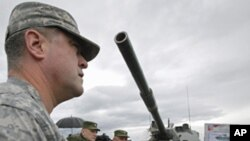 "A US, OSCE military observer examines a newly added to Russia's armory 2S25 ""Sprut-SD"" heavy armament combat vehicle, Sept. 23, 2011."