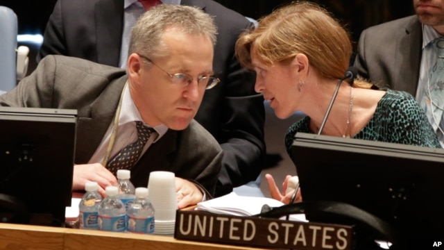 U.S. Ambassador Samantha Power talks with British delegate Michael Tatham during a United Nations Security Council meeting at U.N. headquarters in New York,  Aug. 29, 2013.
