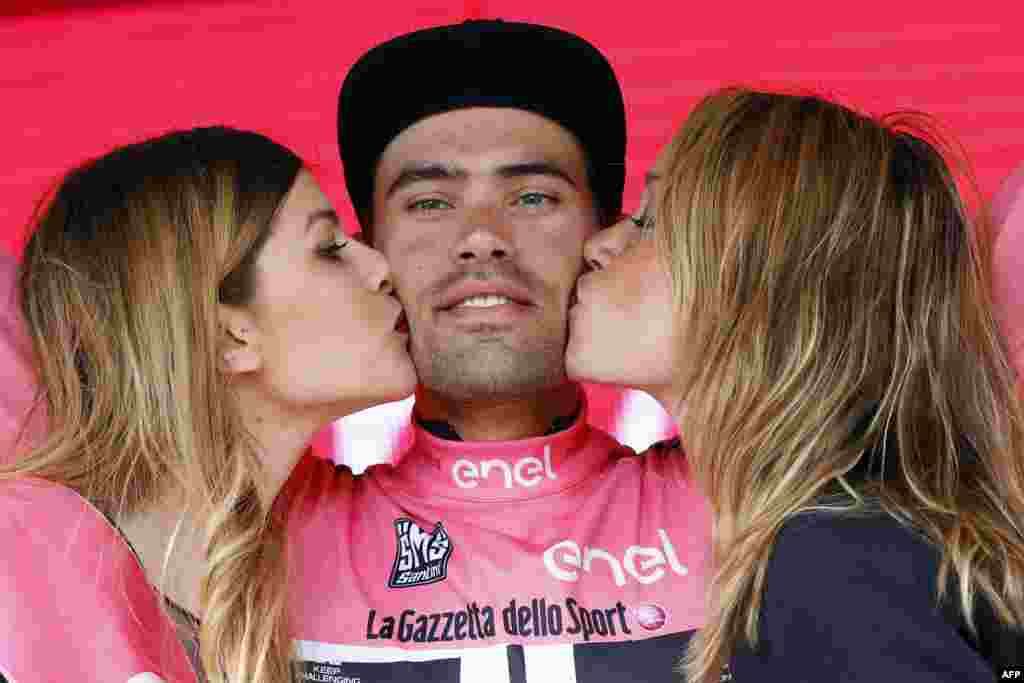 Two hostesses kiss Dutch cyclist Tom Dumoulin of Giant - Alpecin team as he bears the leader's pink jersey on the podium in the 7th stage of 99th Giro d'Italia, Tour of Italy, from Sulmona to Foligno in Foligno, Italy.