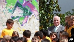 Former German Chancellor Helmut Kohl sits amid pupils next to a piece of the Berlin Wall next to his home in Ludwigshafen August 9, 2011.