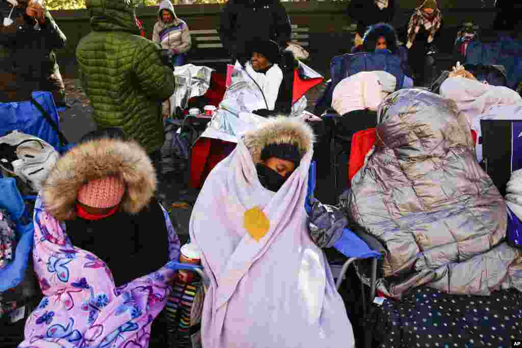 People try to stay warm as they wait for the start of the 92nd annual Macy's Thanksgiving Day Parade in New York.