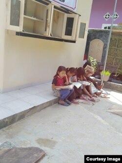 Anak-anak belajar membaca dengan buku dan majalah anak-anak di desa Rawajaya, Cilacap. Courtesy Ari Hendra Permana.