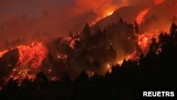 Aliran lava tampak mengalir keluar dari gunung berapi di Taman Nasional Cumbre Vieja di El Paso, Pulau Palma, Kepulauan Canary pada 19 September 2021 dalam gambar yang merupakan potongan dari video meletusnya gunung tersebut. (Foto: FORTA/Handout via Reuters)