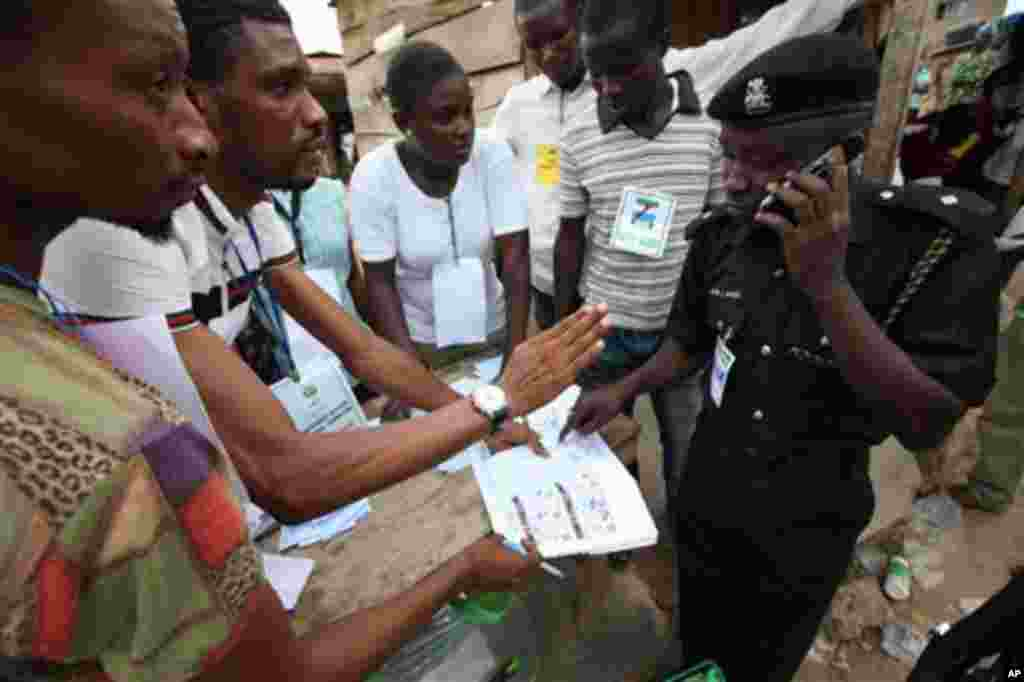 A Police officer, right, checks election results from electoral officers after the National Assembly election in Ibadan, Nigeria,Saturday, April 9, 2011.