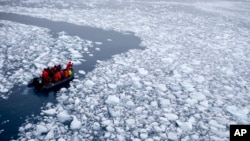 FILE - In this Jan. 22, 2015 photo, a zodiac carrying a team of international scientists heads to Chile's station Bernardo O'Higgins, Antarctica. Water is eating away at the Antarctic ice, melting it where it hits the oceans. (AP Photo/Natacha Pisarenko)