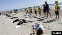 Các nhà hoạt động thuộc Tổ chức Ân xá Quốc tế tham gia 1 buổi diễn trên bãi biển để kỷ niệm ngày Người Tị nạn Thế giới tại Valencia, Tây Ban Nha, 20/6/2015.