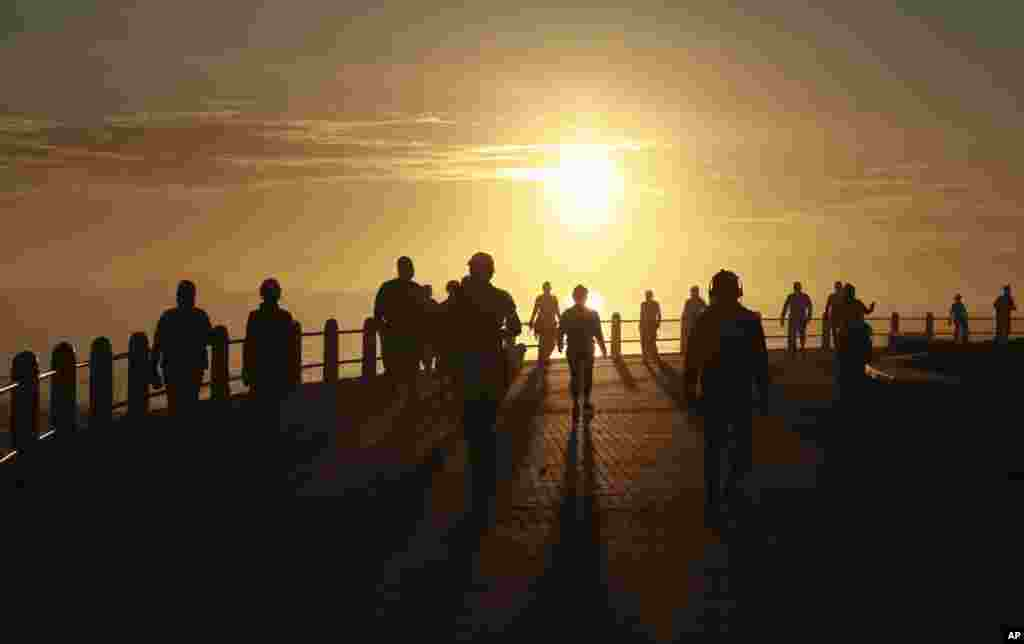 People exercise at sunrise in Sea Point, Cape Town, South Africa as the country marks day 53 of a government lockdown in a bid to prevent the spread of coronavirus.