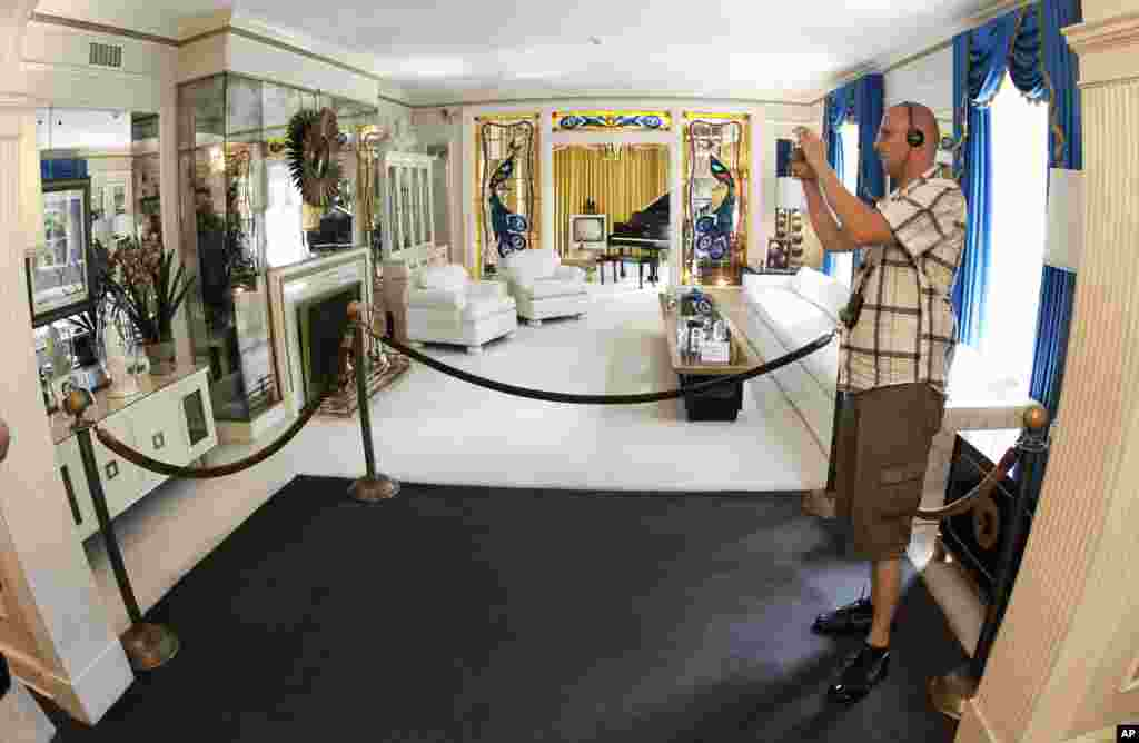 This Aug. 2010 photo shows a tourist viewing the living room at Graceland, Elvis Presley's home in Memphis, Tenn. Graceland opened for tours on June 7, 1982. They sold out all 3,024 tickets on the first day.