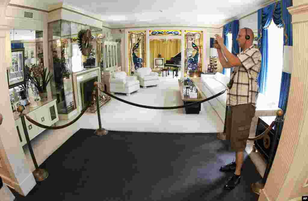 Ova fotografije iz avgusta 2010. pokazuje turistu kako gleda dnevnu sobu u Grejslendu. Elvisova vila u Memfisu u državi Tenesi otvorena za turiste 7. juna, 1982. Prvog dana otvaranja Grejslenda rasprodate se sve ulaznice, za ukupno 3.024 posetioca.