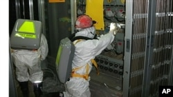 Workers wearing protective suits check the status of the water level indicator at the fuel area inside the crippled Fukushima Daiichi Nuclear Power Plant Number 1 reactor in Fukushima Prefecture May 10, 2011 in this handout photo released by TEPCO, May 12