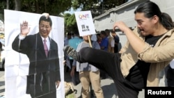 Một nhà hoạt động Đài Loan giơ chân đạp vào hình của Chủ tịch Trung Quốc Tập Cận Bình trong một cuộc biểu tình phản đối cuộc họp sắp tới giữa Tổng thống Đài Loan với ông Tập tại Đài Bắc, ngày 5/11/2015.