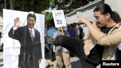 ນັກເຄື່ອນໄຫວຄົນໜຶ່ງສະແດງທ່າທາງຖີບເຕະຢູ່ຕໍ່ໜ້າຮູບຂອງປະທານປະເທດ ຈີນ ທ່ານ Xi Jinping ໃນລະຫວ່າງ ການປະທ້ວງ ຕໍ່ກອງປະຊຸມທີ່ໃກ້ຈະມາເຖິງນີ້ ລະຫວ່າງ ປະທານາທິບໍດີ ໄຕ້ຫວັນ ທ່ານ Ma Ying-jeou ແລະ ປະທານປະເທດ ຈີນ ທ່ານ Xi Jinping, ຢູ່ໜ້າຫ້ອງການປະທານາທິບໍດີໃນ ໄຕ້ຫວັນ. 5 ພະຈິກ, 2015.