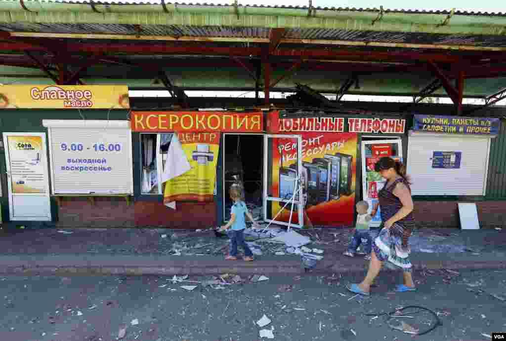Seorang perempuan dan anak-anak berjalan melewati jalanan pasar yang rusak di Slovyansk, Ukraina Timur (1/7).