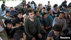 Người Uighur từ Tân Cương ngồi bên trong nơi trú ẩn tạm thời sau tại trụ sở di trú gần biên giới Thái Lan-Malaysia.