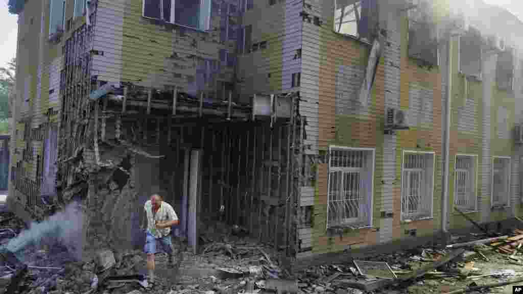 A man runs out of the destroyed building after shelling in Donetsk, eastern Ukraine, Aug. 10, 2014.