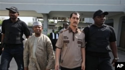 Azim Aghajani, an Iranian citizen, second right, and Nigerian Usman Abbas Jega, second left charged with orchestrating an illegal arms shipment into Nigeria are escorted at the Federal Hight Court in Lagos, Nigeria.