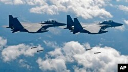 FILE - In this photo provided by South Korea Defense Ministry, South Korean air force F-15K fighter jets drop bombs as they fly over the Korean Peninsula during a joint drills with the U.S., Sept. 18, 2017. On Thursday, the air force said one of its F-15K jets crashed at a mountain in the country's rural south.