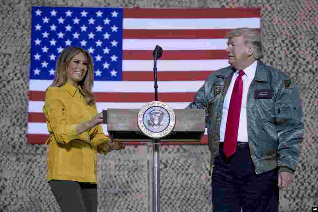 La primera dama Melania Trump, a la izquierda, y el presidente Donald Trump permanecen juntos en el escenario durante un mitin en la base aérea Al Asad, Irak.