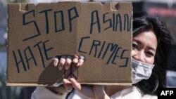 一名示威者在洛杉矶中国城附近手举标语牌参加反对针对亚裔暴力犯罪的活动。(2021年2月20日)