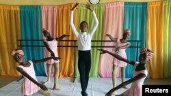 Anthony Mmesoma Madu, 11 anos, bailarino nigeriano, rodeado de bailarinas na escola Leap of Dance Academy, em Lagos