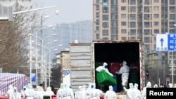 身穿防护服的工人在清理清理武汉华南海鲜市场。这里曾被认为是新冠病毒的发源地。(2020年3月4日)