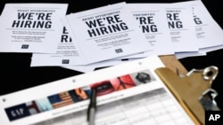 FILE - Job applications and information for the Gap Factory Store sit on a table during a job fair at Dolphin Mall in Miami, Oct. 6, 2015.