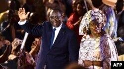 Le président sortant Macky Sall (à gauche) et son épouse Marieme Faye Sall (à droite) saluent les spectateurs à la cérémonie de son investiture comme candidat à la prochaine élection présidentielle, à Dakar, le 1er décembre 2018,