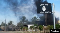 FILE - Smoke raises behind an Islamic State flag in Diyala province, Iraq, Nov. 24, 2014.