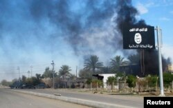 FILE - Smoke raises behind an Islamic State flag in Iraq, Nov. 24, 2014.
