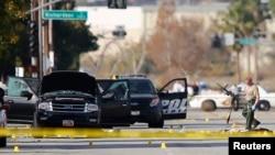Un policier ramasse une arme près du véhicule à bord duquel était le couple des auteurs présumés de la fusillade de San Bernardino qui ont été abattus, en Californie, 3 décembre 2015.