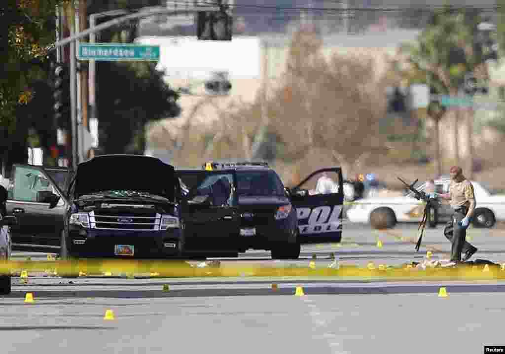 Seorang polisi membawa senjata dari lokasi penyelidikan di sekitar kawasan mobil SUV di mana dua tersangka ditembak polisi setelah penembakan massal di San Bernardino, California. Pemerintah sedang menyelidiki kenapa Syed Rizwan Farook, 28, dan Tashfeen Malik, 27, melepaskan tembakan di sebuah pesta akhir tahun rekan kerjanya di California selatan, menewaskan 14 orang dan melukai 17 orang dalam sebuah serangan yang tampaknya telah direncanakan itu.